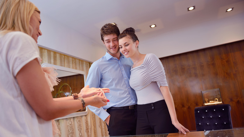 happy young romantic couple in love buy jewelry ring in luxury store