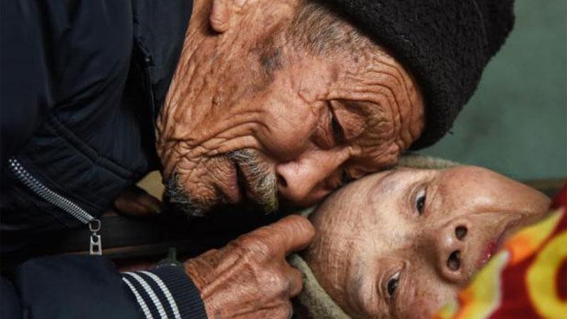 Kilka miesięcy po ślubie Zhou została sparaliżowana. Jej młody mąż rzucił wszystko, by się nią zająć i mimo ciężkich warunków, robi to już od... 56 lat!